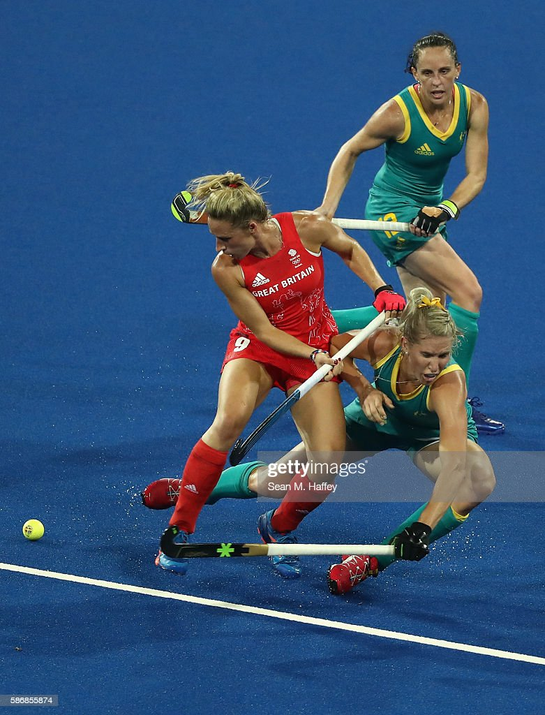 Susannah Townsend of Great Britain collides with Jodie Kenny and Madonna Blyth of Australia during a Women's Pool B match between Australia and Great...