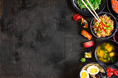 Sushi and japanese food on dark background. Sushi rolls, hiyashi wakame, miso soup, ramen, fried rice with vegetables, nigiri, salmon steak, soy sauce, сhopsticks. Asian/Japanese food frame. Overhead