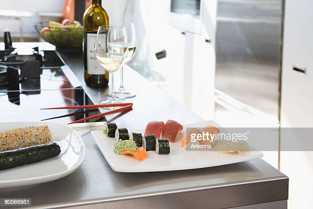 Sushi and white wine on a kitchen bench