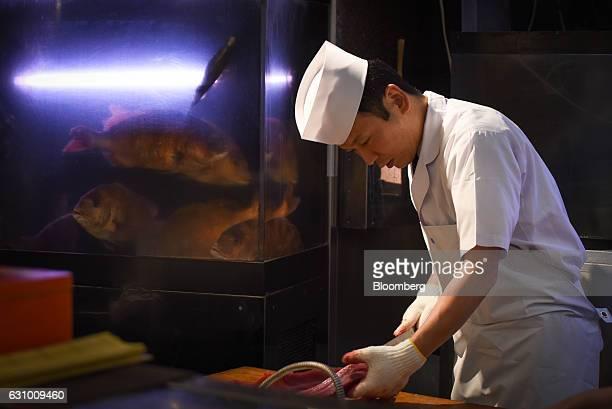 A sushi chef cuts a tuna at a Sushi Zanmai restaurant in Tokyo Japan on Thursday Jan 5 2017 Kiyomura KK operator of Sushi Zanmai restaurant made the...