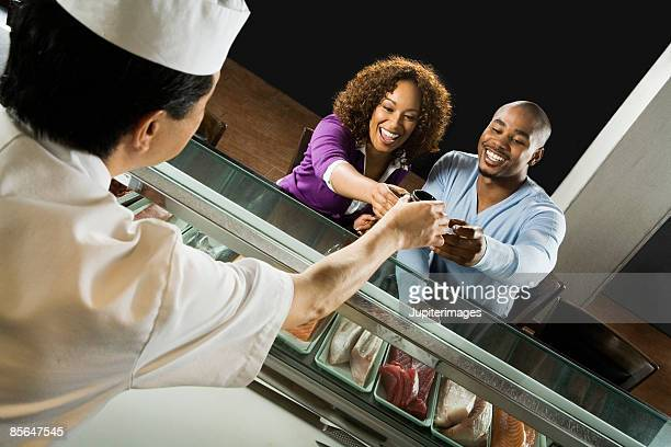 Sushi chef giving sushi to couple