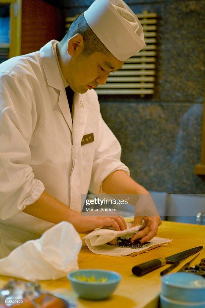 Sushi chef preparing dish in small Ginza top floor restaurant.