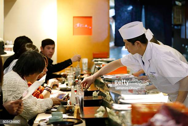 A sushi chef serves a piece of sushi at a Sushi Zanmai sushi restaurant operated by Kiyomura KK after the year's first auction at Tsukiji Market on...