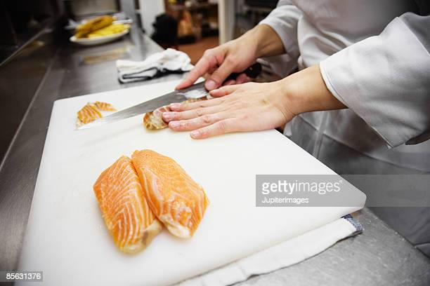 Sushi chef slicing fish