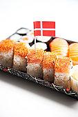 Sushi food on tray with Danish flag against white background