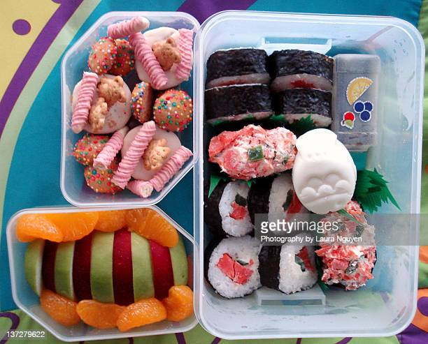 Sushi, fruit, and sweets bento box lunch