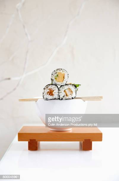 Sushi resting on bowl on white table