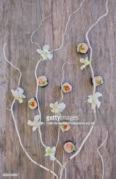 Sushi rolls and flowers on table