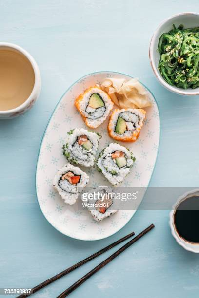 Sushi rolls on a plate, Wakame seaweed salad and green tea