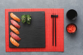 Salmon sushi on black slate plate. Black saucer with soy sauce, ginger in small bowl, chopsticks on red bamboo mat. Flat lay, copy space, grey background, top view