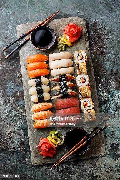 Sushi Set nigiri and sushi rolls served for two on gray stone slate on metal background