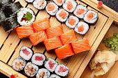Japanese cuisine. Sushi set on a wooden plate and dark concrete background.