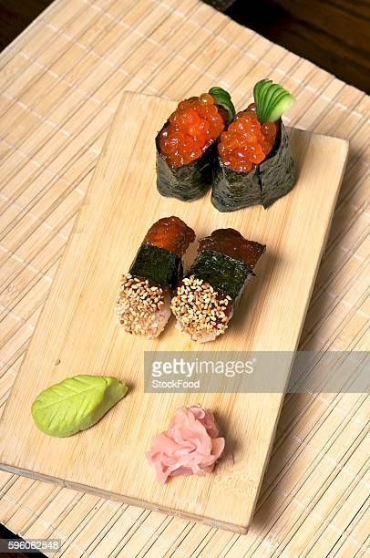 Sushi with mackerel and salmon caviar on a wooden board