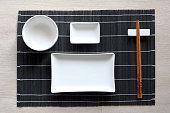 Japanese table setting with traditional mat and sushi kit. Top view