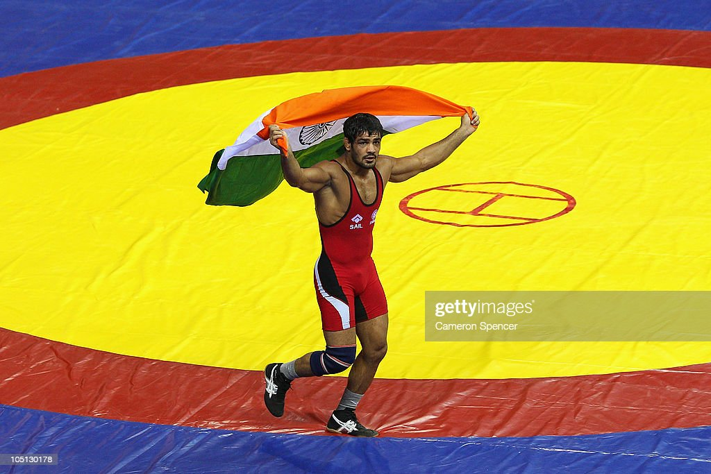 <a gi-track='captionPersonalityLinkClicked' href=/galleries/search?phrase=Sushil+Kumar+-+Wrestler&family=editorial&specificpeople=703954 ng-click='$event.stopPropagation()'>Sushil Kumar</a> of India runs a lap of honour after winning against Heinrich Barnes of South Africa in the men's 66kg freestyle gold medal wrestling at IG Sports Complex during day seven of the Delhi 2010 Commonwealth Games on October 10, 2010 in Delhi, India.