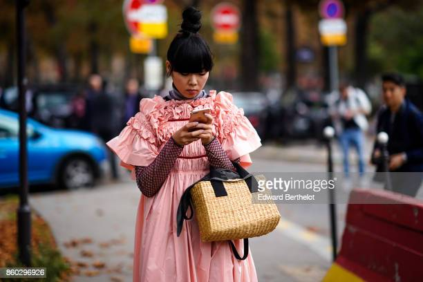 Susie Lau wears a pink gathered dress a turtleneck top with fishnet sleeves a straw bag outside Lanvin during Paris Fashion Week Womenswear...