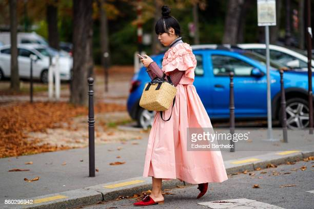 Susie Lau wears a pink gathered skirt a turtleneck top with fishnet sleeves a straw bag red slides with a burgundy bow outside Lanvin during Paris...