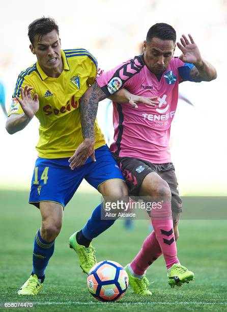 Suso Santana of CD Tenerife competes for the ball with Brian Olivan of Cadiz CF during La Liga Segunda Division between Cadiz CF and CD Tenerife at...