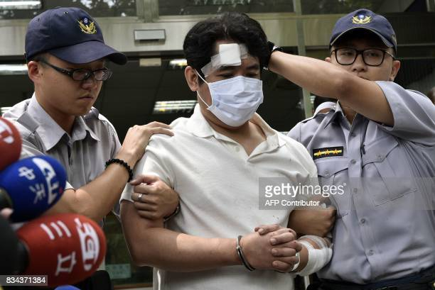 A suspect identified only by his family name Lu is escorted by policemen at a local police bureau in Taipei on August 18 after he was suspected of...