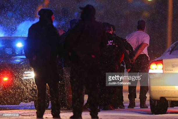 A suspect is led away in handcuffs by police during an active shooter situation outside a Planned Parenthood facility where an active shooter...