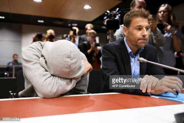TOPSHOT Suspect Mohamed Bakier allegedly involved in the Finnish stabbing attack covers himself next to jis lawyer Joni Brander in the Southwest...