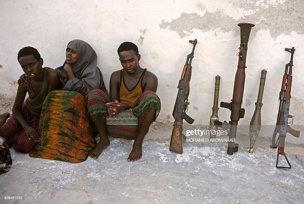 Suspected Al Qaeda-aligned Shabaab militants, a woman and her three children, sit next to weapons after their arrest on May 5, 2016 in Mogadishu. Somali security forces presented to journalists a family suspected of belonging to the Somalia-based al-Qaeda affiliated Islamist militant group Al-Shabaab. Members of this family were arrested with two AK-47 assault rifles and a rocket during an operation by Somali security forces against suspected members of of Somalia's Shebab Islamists in the capital Mogadishu. / AFP / MOHAMED