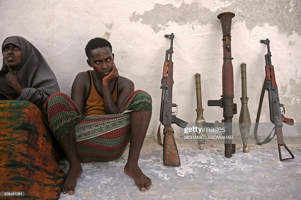 Suspected Al Qaeda-aligned Shabaab militants, a woman and one of her children, sit next to weapons after their arrest on May 5, 2016 in Mogadishu. Somali security forces presented to journalists a family suspected of belonging to the Somalia-based al-Qaeda affiliated Islamist militant group Al-Shabaab. Members of this family were arrested with two AK-47 assault rifles and a rocket during an operation by Somali security forces against suspected members of of Somalia's Shebab Islamists in the capital Mogadishu. / AFP / MOHAMED