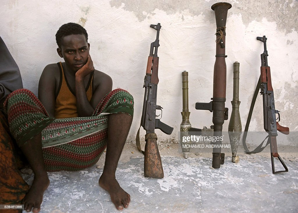 Suspected Al Qaeda-aligned Shabaab militants man sits next to weapons after his arrest on May 5, 2016 in Mogadishu. Somali security forces presented to journalists a family suspected of belonging to the Somalia-based al-Qaeda affiliated Islamist militant group Al-Shabaab. Members of this family were arrested with two AK-47 assault rifles and a rocket during an operation by Somali security forces against suspected members of of Somalia's Shebab Islamists in the capital Mogadishu. / AFP / MOHAMED