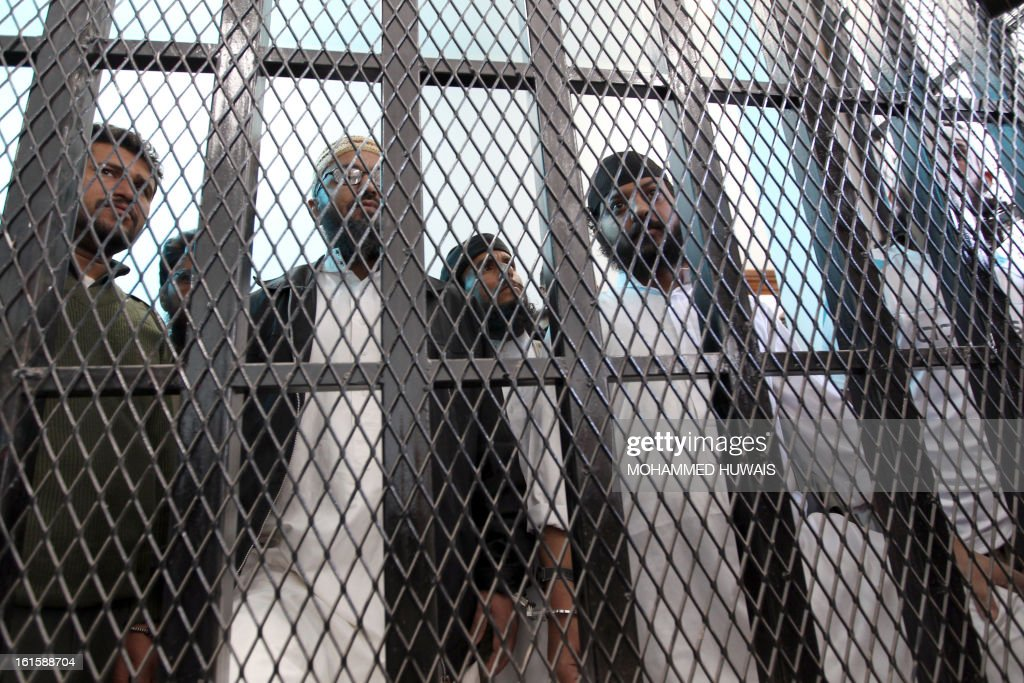 Suspected al-Qaeda militants being held in a barred caged listen on as their sentences are handed down by a judge at the state security appeals court in the capital Sanaa, on February 12, 2013. Twenty four suspects were indited to various prison terms.