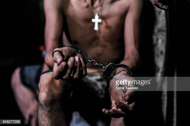 A suspected drug user is handcuffed during a night time raid on a drug den on June 16 2016 in Manila Philippines The presidentelect of the...
