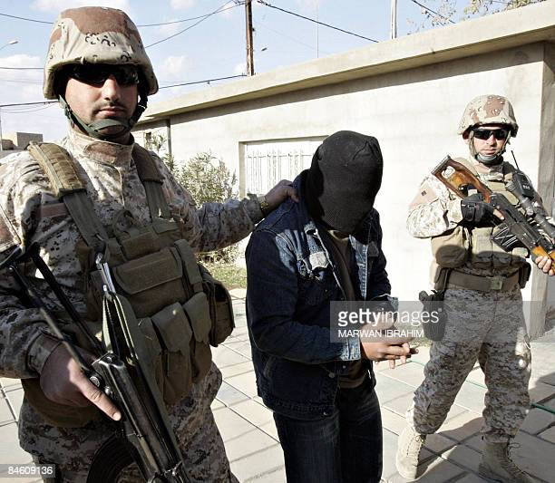 Suspected insurgents are escorted by Kurdish soliders at a Peshmerga military camp in Kirkuk 255 kms north of the capital Baghdad on February 3 2009...