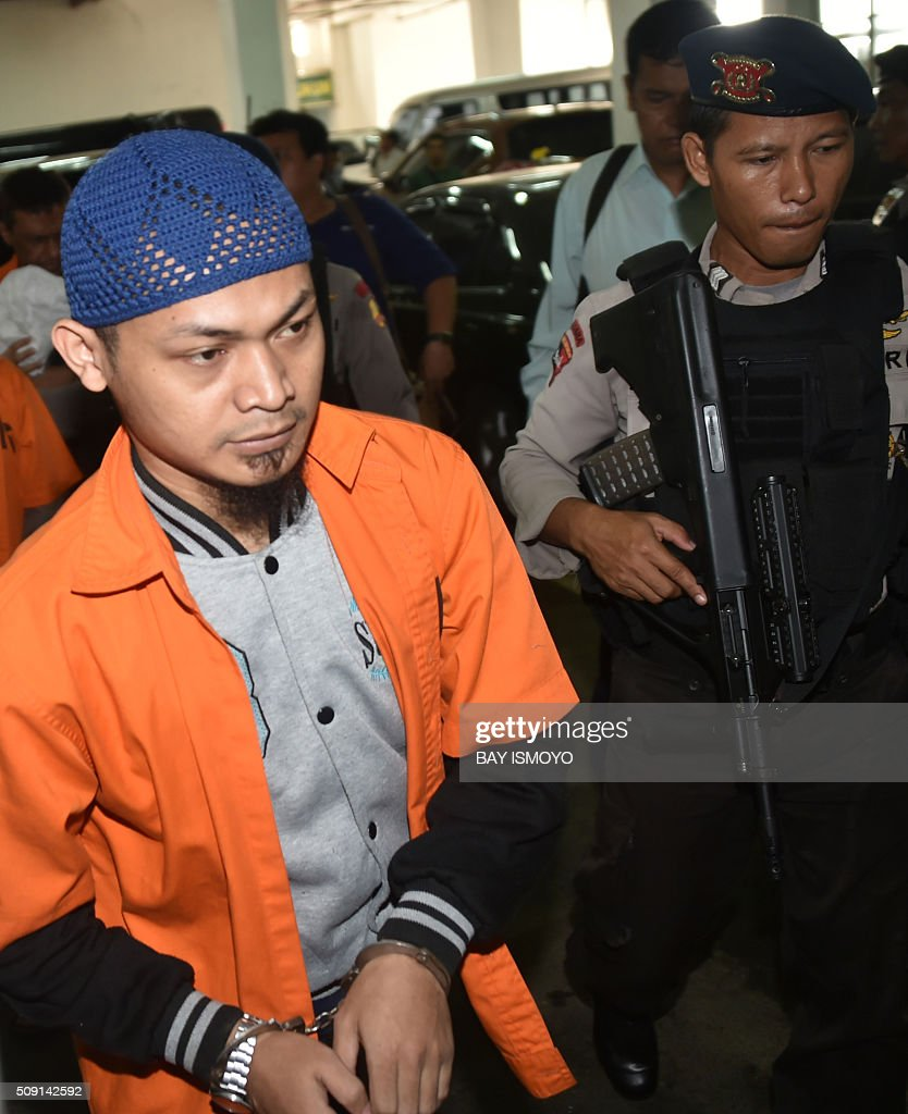 Suspected Islamic radical identified as Koswara (L) is escorted by Indonesian armed police as he is brought to court in Jakarta on February 9, 2016. An Indonesian court February 9 sentenced seven men to between three and five years in jail for supporting the Islamic State group, weeks after the extremist network launched a deadly assault on Jakarta. AFP PHOTO / Bay ISMOYO / AFP / BAY ISMOYO