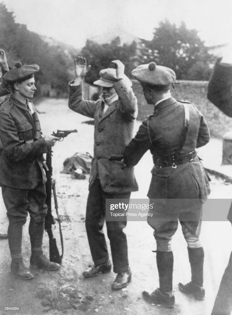 A suspected member of the Irish nationalist party Sinn Fein is searched at gunpoint by temporary constables of the British Black and Tans during the...