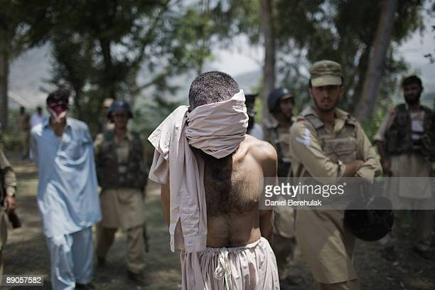 Suspected Taliban militants are held before being interrogated by the Pakistan Military at a Military outpost after capturing them on a security...