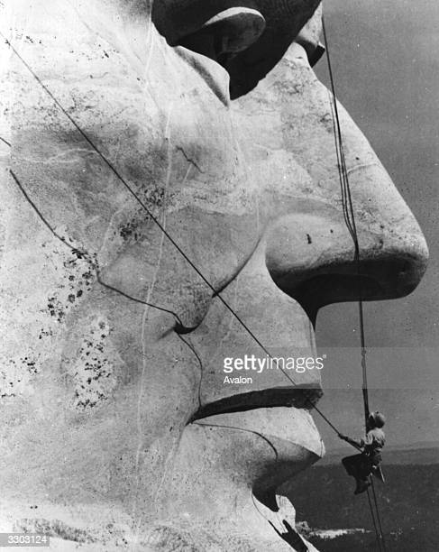 A suspended maintenance man working under the nose of President Lincoln at Mount Rushmore South Dakota