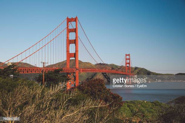 Suspension Bridge Over River Against Blue Sky
