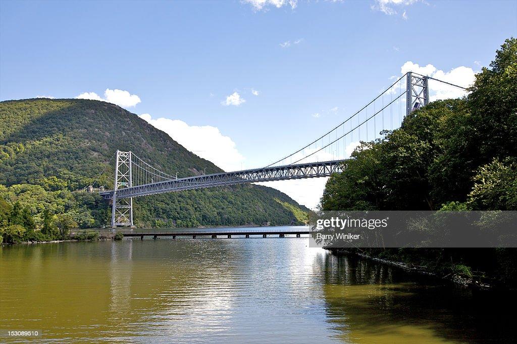 Suspension bridge over river near mountain.