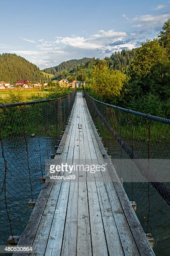 Suspension bridge over the river in the mountains : Stock Photo