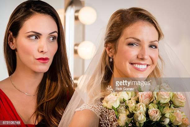 Suspicious bridesmaid standing behind smiling bride