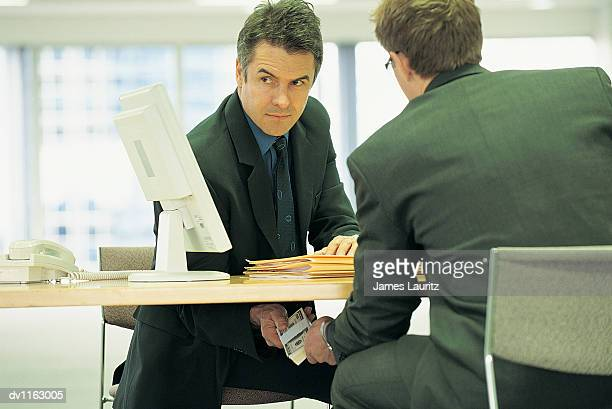 Suspicious Businessman Passing a Bundle of Banknotes Under a Table to a Colleague