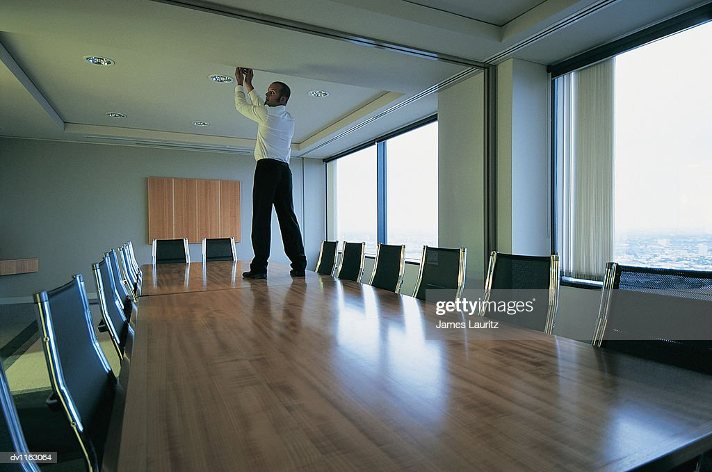 Suspicious Businessman Standing on a Table in a Conference Room Reaching up to the Ceiling : Stock Photo