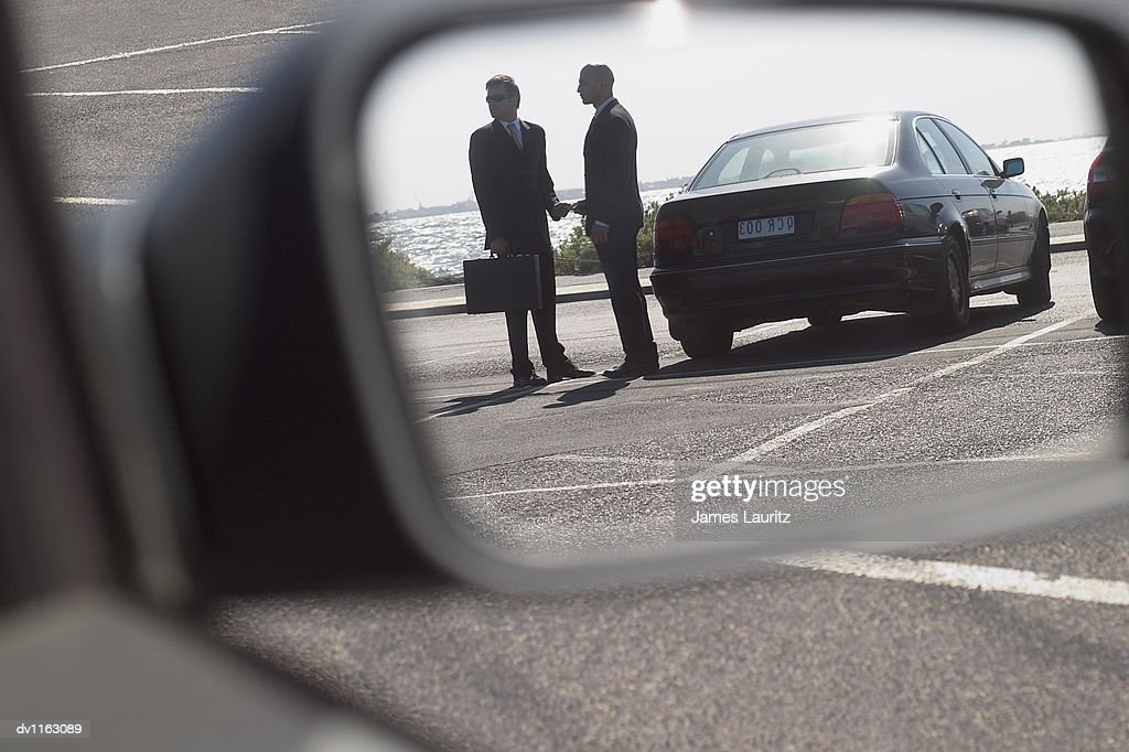 Suspicious Businessmen in a Carpark Giving and Recieving a Bribe : Stock Photo