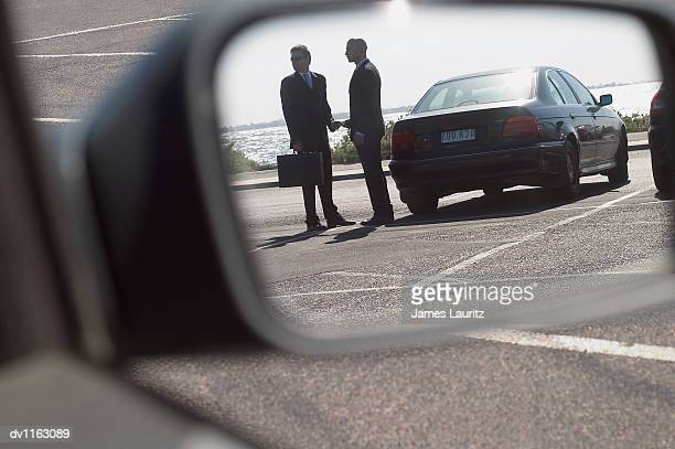 Suspicious Businessmen in a Carpark Giving and Recieving a Bribe