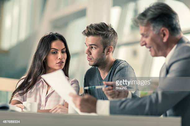 Suspicious couple having a business meeting with real estate agent.