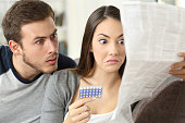 Suspicious couple reading a leaflet after taking contraceptive pills sitting on a couch in the living room at home