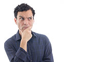 A suspicious man has his hands resting on his chin. He looks to the side. The person is Caucasian and is wearing blue button-down shirt. Isolated. White background.