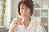 Suspicious middle age woman looking glass of water