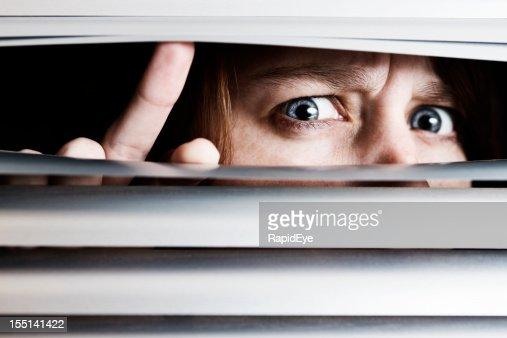 Suspicious nervous young woman peeps through venetian blinds