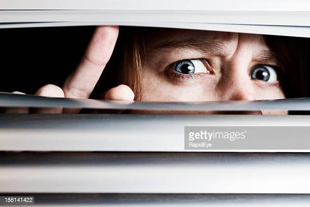 Suspicious nervous young woman peeps through venetian blinds