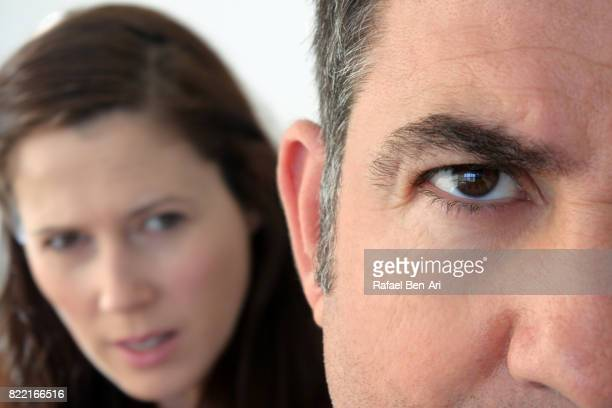 Suspicious wife looks at her husband